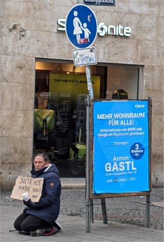 Obdachloser in München neben CSU Plakat